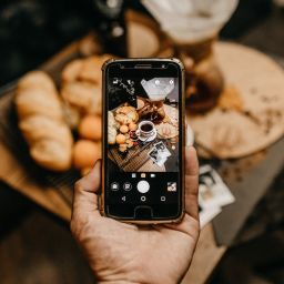 Cell phone taking a picture of coffee and pastries
